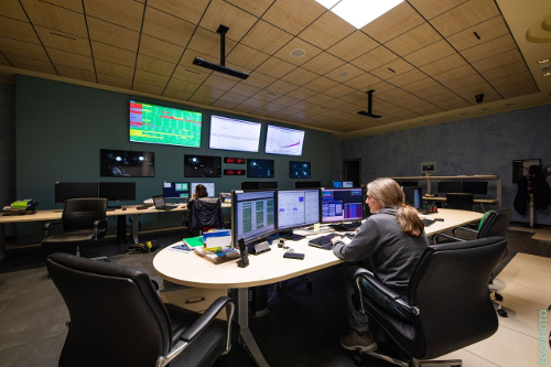 The control room of Advanced Virgo at the European Gravitational Observatory, near Pisa (Italy). Shown in the foreground is an EGO operator working on shift to keep the detector running. Usually a lively environment, the control room is now minimally populated because of the COVID-19 pandemic. The image shows only one Virgo scientist working, Julia Casanueva, in the control room along with the EGO operator, Fabio Gherardini.  Image credit: EGO/Virgo Collaboration